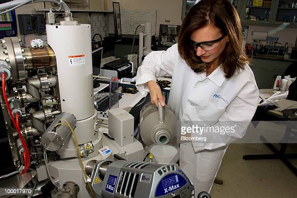 Jeni Thomas a senior scientist at Procter Gamble Co's beauty research facility pours liquid nitrogen into an electron microscope at a PG laboratory...