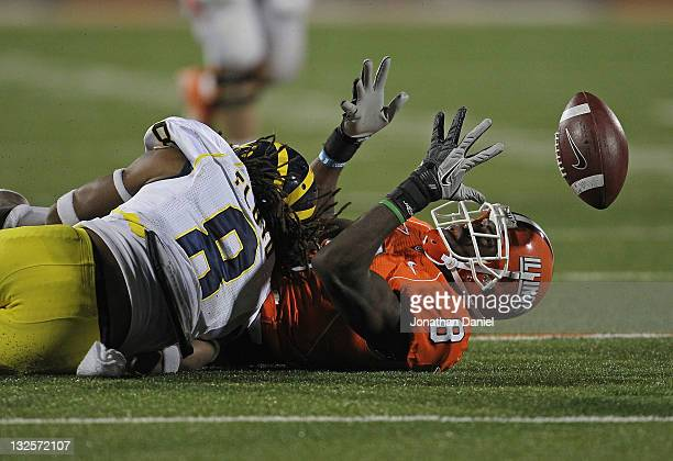 Jenkins of the Illinois Fighting Illini can't hold on to the ball after being hit by J.T. Floyd of the Michigan Wolverines at Memorial Stadium on...