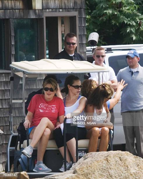 Jenna Bush and Barbara Bush daughters of US President George W Bush ride in the back of a golf cart driven by their grandfather former US president...