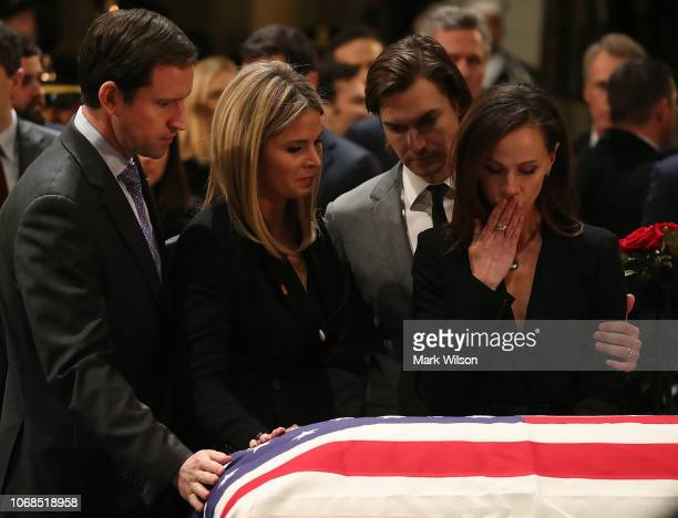 Jenna Bush Hager and her sister Barbara Bush stand with the husbands Henry Chase Hager and Craig Coyne as they pay respect in front of the casket of...