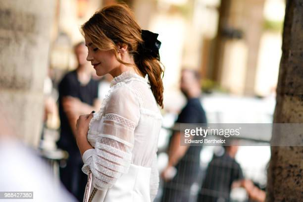 Jenna Coleman wears a white mesh lace dress outside the Miu Miu Cruise Collection show outside the Hotel Regina in Paris on June 30 2018 in Paris...