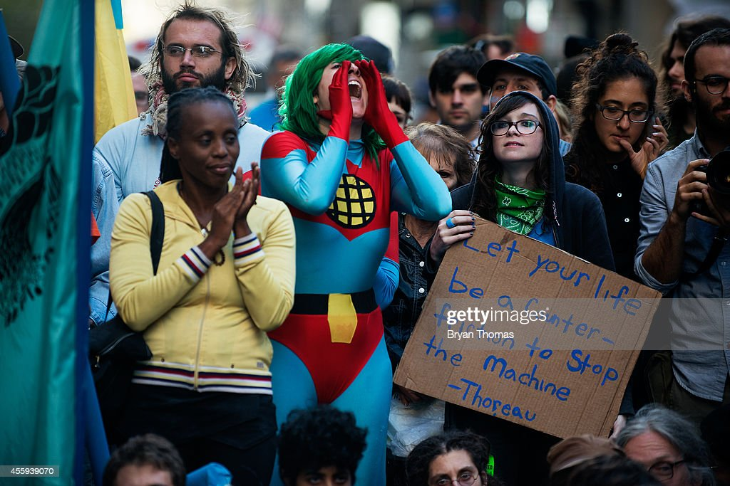 Jenna deBloisblanc (C), 25, dressed as Captain Planet, demonstrates on Broadway during the Flood Wall Street protest on September 22, 2014 in New York City. The Flood Wall Street protest came on the heels of the climate change march on September 21 that attracted over 300,000 protestors.