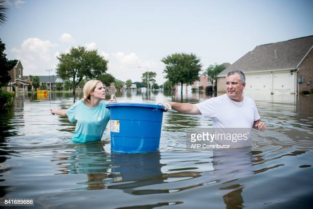 Jenna Fountain and her father Kevin carry a bucket down Regency Drive to try to recover items from their flooded home in Port Arthur Texas September...
