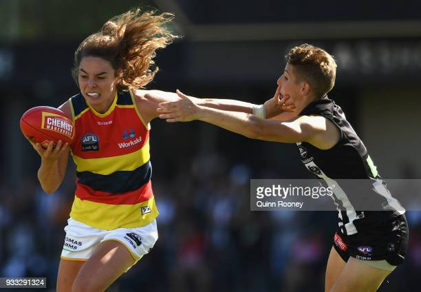 Jenna McCormick of the Crows fends off a tackle by Emma Grant of the Magpies during the round seven AFLW match between the Collingwood Magpies and...