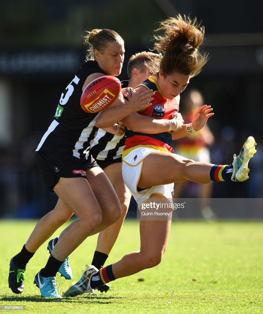 Jenna McCormick of the Crows kicks whilst being tackled by Emma Grant and Meg Hutchins of the Magpies during the round seven AFLW match between the Collingwood Magpies and the Adelaide Crows at Olympic Park on March 18, 2018 in Melbourne, Australia.