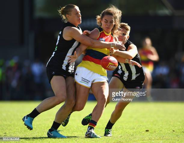 Jenna McCormick of the Crows kicks whilst being tackled by Emma Grant and Meg Hutchins of the Magpies during the round seven AFLW match between the...