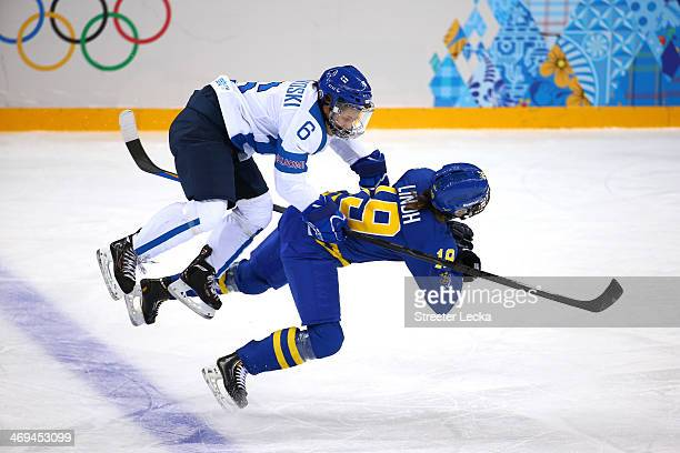 Jenni Hiirikoski of Finland checks Maria Lindh of Sweden during the Women's Ice Hockey Playoffs Quarterfinal game on day eight of the Sochi 2014...