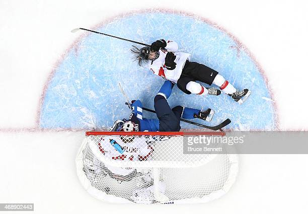 Jenni Hiirikoski of Finland scores the game winning goal in overtime against Florence Schelling of Switzerland to defeat them 4 to 3 in the Women's...
