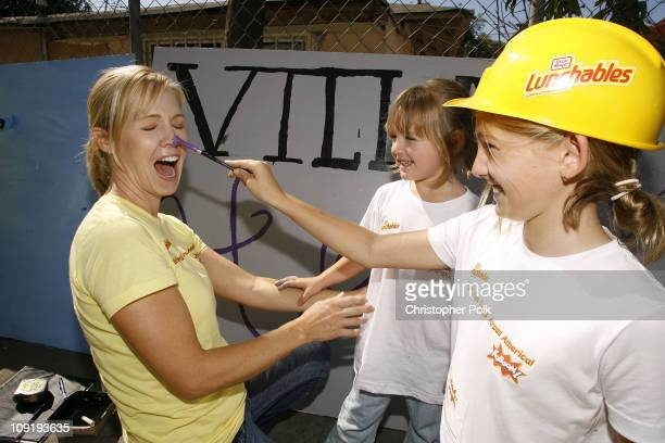 Jennie Garth gets some paint tips from daughters Luca right and Lola center while helping build a new playground with Lunchables and KaBOOM in Los...