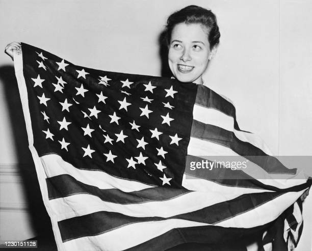 Jennie Irish, of Burlington, secretary of the White House, holds a 50-star American flag, with the two stars added representing Alaska and Hawaii, on...