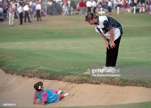 Jennie wife of Ian BakerFinch of Australia talks to their daughter Hayley as she lies in a bunker after her father wins the British Open Golf...