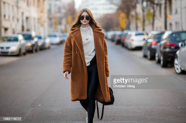 Jennifer Amanda is seen wearing brown teddy coat by Ducie London Colorado sweater by Adidas a shiny black PCP leggings Addict sneakers by Ash...