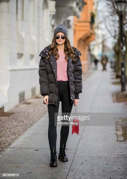 Jennifer Amanda wearing a grey wool hat from Acne a black puffer jacket from Edited a classic black high waist leggings from Fabletics a red white...
