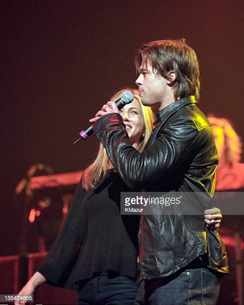 Jennifer Aniston and Brad Pitt show off Jennifer's engagement ring onstage at the Beacon Theater during a Sting concert on Nov 21 1999