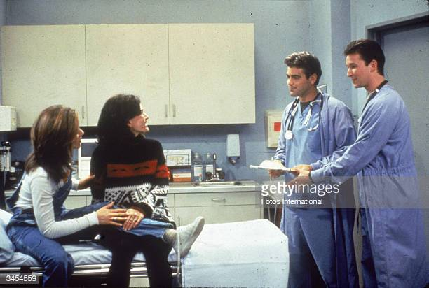 Jennifer Aniston and Courteney Cox sit in a hospital room, speaking to guest stars George Clooney and Noah Wyle from 'ER' in a still from the...