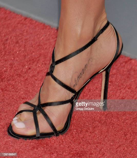 Jennifer Aniston shows her new tattoo on her foot as she arrives at the Los Angeles Premiere of Horrible Bosses at the Grauman's Chinese Theatre on...