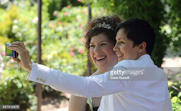 TORONTO ON JUNE 26 Jennifer Atkins and Susan Justin take a selfie before a Mass wedding was held at in the gardens at Casa Loma as part of Pride...