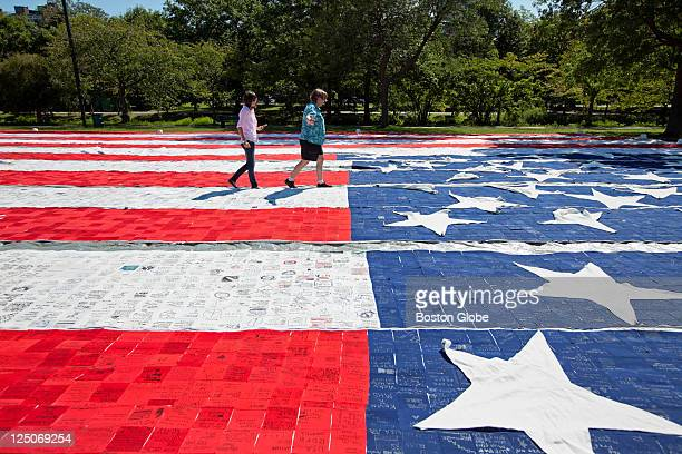 Jennifer Baily of Medford walks across a pathway on the flag with exchange student Clara Blanco of Segovia Spain The 'United We Stand for America A...