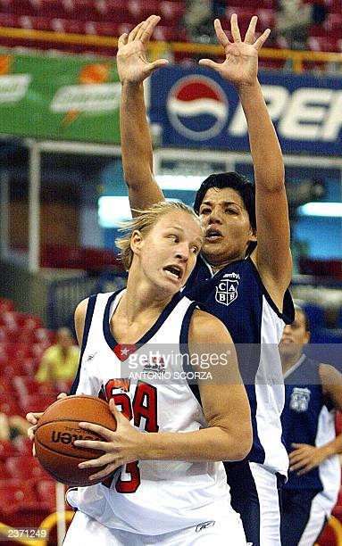 US Jennifer Benningfield tries to elude blocking Erica Sanchez of Argentina during their women's basketball match 05 August 2003 at the XIV...