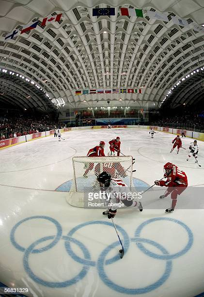 Jennifer Botterill of Canada brings the puck around the net in front of Kristina Petrovskaya of Russia during the women's ice hockey Preliminary...