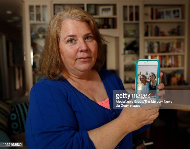 Jennifer Carole poses for a photograph with a photograph on her phone of her father Lyman Smith and stepmother Charlene Smith in her home in Santa...