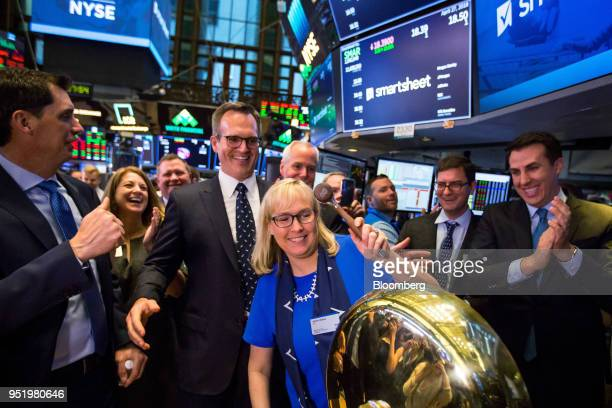 Jennifer Ceran chief financial officer at Smartsheetcom Inc center rings a ceremonial bell as Mark Mader president and chief executive officer of...