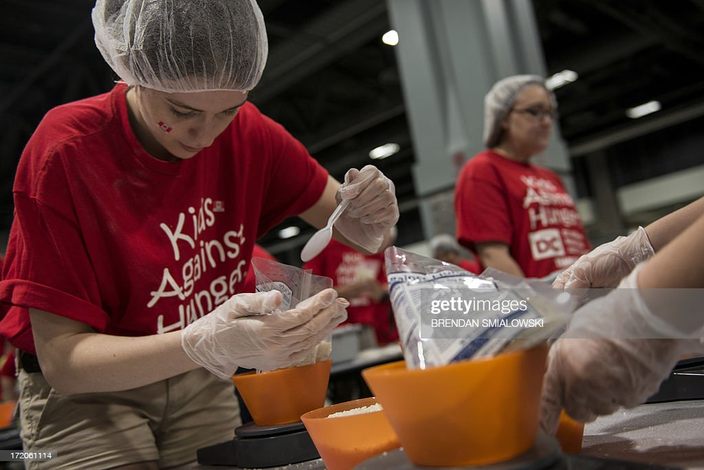 Jennifer Donlop, of Ontario, Canada, adjusts the weight of a meal pack at the Washington Convention Center July 1, 2013 in Washington, DC. The event, organized by Kids Against Hunger, organized volunteers into teams to assemble and pack a goal of 1 million meals which would be kept with local charities and sent overseas. AFP PHOTO/Brendan SMIALOWSKI