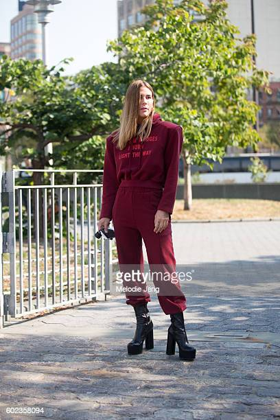Jennifer Grace wears a red Vetements 'May The Bridges I Burn Light The Way' hoodie and sweatpants and black high platform boots outside the Lacoste...