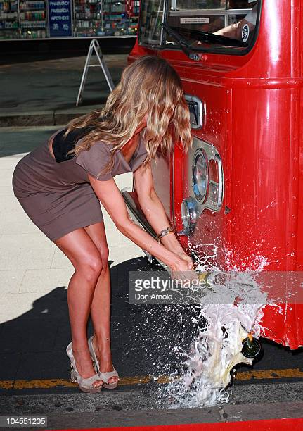 Jennifer Hawkins smashes a bottle of champagne against the Vodafone bus during the launch for the new Vodafone Campaign at Customs House on September...