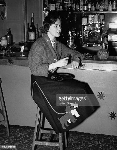 Jennifer Hill relaxes with a drink in the bar of the Bear Hotel She wears a black felt skirt decorated with two appliques felt dogs and a short...