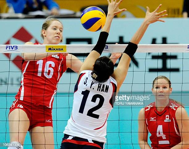 Jennifer Hinze of Canada spikes the ball over Han SongYi of South Korea as Canadian captain Tammy Louise Mahon looks on during their first round...
