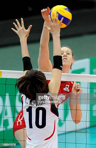 Jennifer Hinze of Canada spikes the ball over Kim YeonKoung of South Korea during their first round match of the World Women's Volleyball...