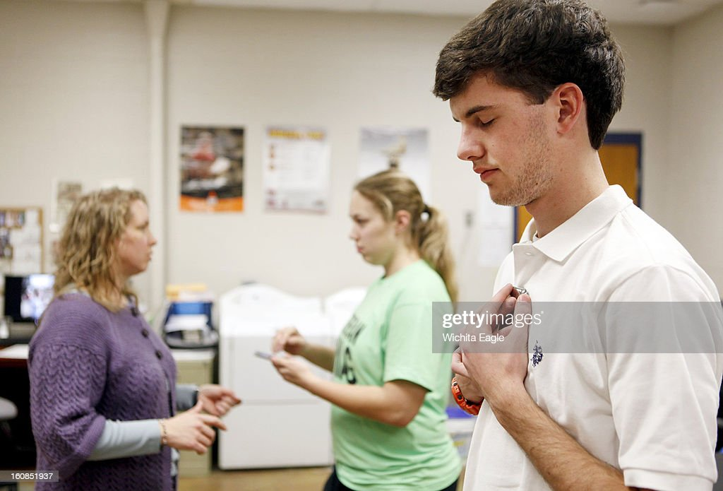 Jennifer Hudson, the head athletic trainer for the Wichita school district, tests the 'Sway Balance' app on Wichita East High School student athletes Eileen Vlamis, center, and Jacksen Petersen in Wichita, Kansas on January 30, 2013.