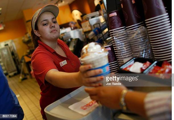 Jennifer Iglesis hands a customer a 99 cent Dunkin' Donuts latte February 26 2008 in Miami Florida On the same day that Dunkin' Donuts offered their...
