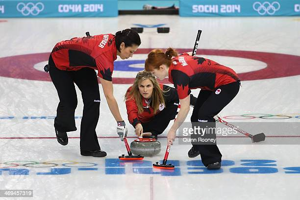 Jennifer Jones of Canada delivers the stone as Jill Officer and Dawn McEwen of Canada sweep the ice during Curling Women's Round Robin match between...