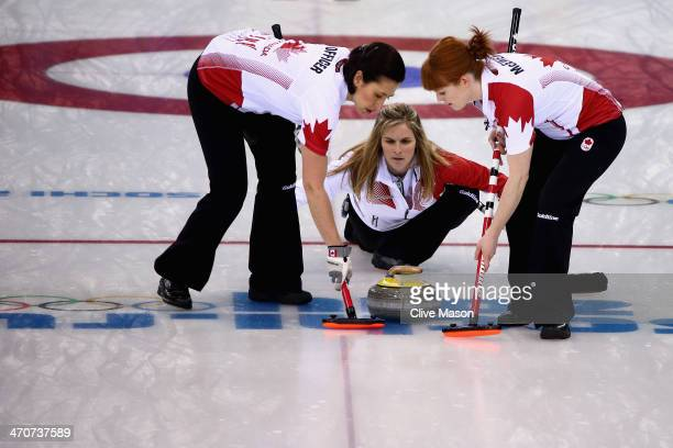 Jennifer Jones of Canada places a stone while Jill Officer and Dawn McEwen of Canada sweep during the Gold medal match between Sweden and Canada on...