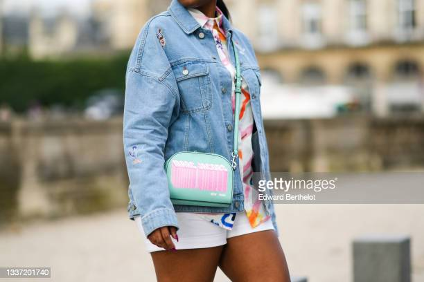 Jennifer Joseph wears a white with multicolored paint pattern shirt, a blue faded denim oversized jacket with multicolored yoke representing...