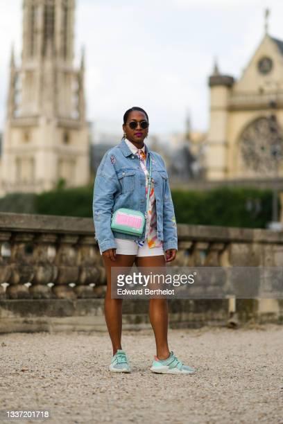 Jennifer Joseph wears black sunglasses, gold large pendant earrings, a white with multicolored paint pattern shirt, a blue faded denim oversized...