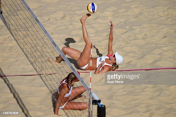 Jennifer Kessy of the United States kicks the ball over the net as April Ross of the United States looks on during the Women's Beach Volleyball Round...