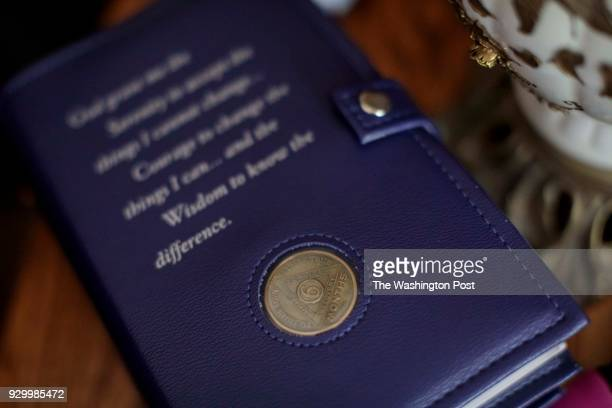 Jennifer Kostoff's sixmonth sobriety coin and her copy of Alcoholics Anonymous The Big Book lies on a table at her Granite City Illinois home on July...