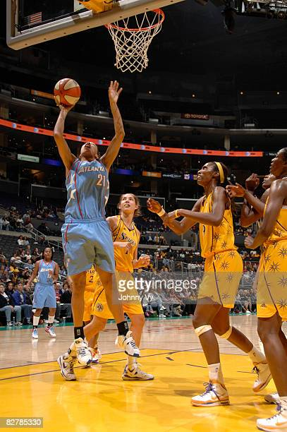 Jennifer Lacy of the Atlanta Dream goes up for a layup while Didney Spencer and Lisa Leslie of the Los Angeles Sparks watch during a game on...