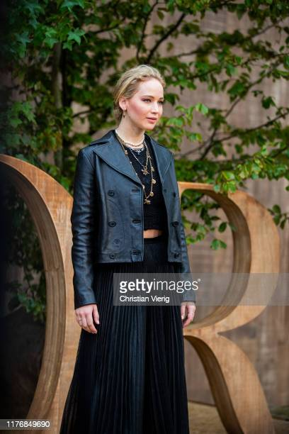 Jennifer Lawrence is seen wearing black pleated skirt cropped top leather jacket necklace at the Dior show on September 24 2019 in Paris France