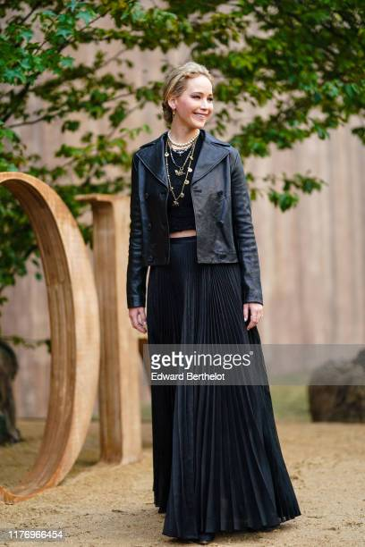 Jennifer Lawrence wears a black leather jacket a golden necklace a black top a black pleated skirt earrings outside Dior during Paris Fashion Week...