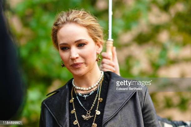 Jennifer Lawrence wears earrings necklaces a black lace crop top a black leather jacket outside Dior during Paris Fashion Week Womenswear Spring...