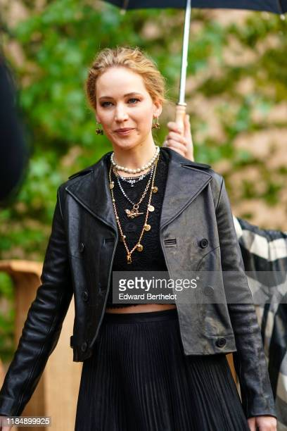 Jennifer Lawrence wears earrings necklaces a black lace crop top a black leather jacket a black pleated skirt outside Dior during Paris Fashion Week...