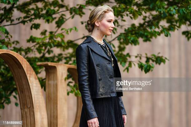 Jennifer Lawrence wears earrings necklaces a black lace crop top a Dior black leather jacket a black pleated skirt outside Dior during Paris Fashion...