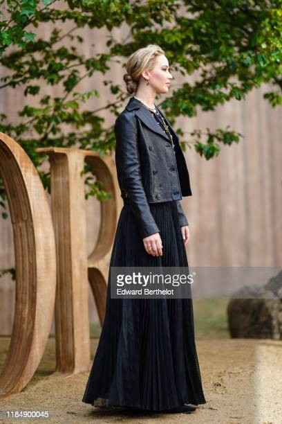 Jennifer Lawrence wears earrings necklaces a black lace crop top a Dior black leather jacket a black flowing long pleated skirt outside Dior during...