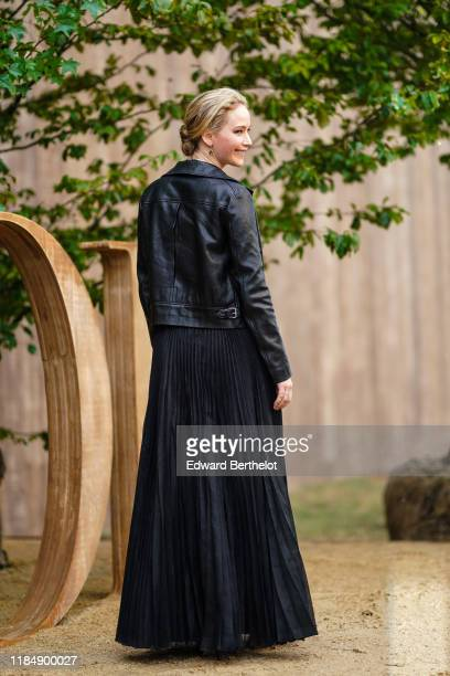 Jennifer Lawrence wears earrings necklaces a black leather jacket a black flowing long pleated skirt outside Dior during Paris Fashion Week...