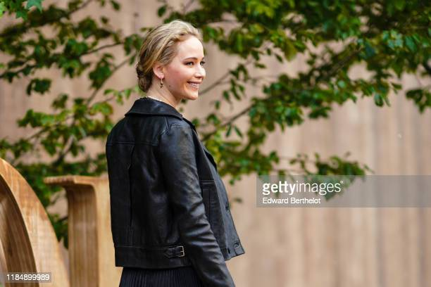 Jennifer Lawrence wears earrings necklaces a Dior black leather jacket outside Dior during Paris Fashion Week Womenswear Spring Summer 2020 on...