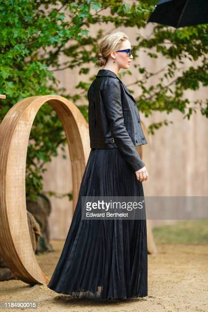 Jennifer Lawrence wears earrings sunglasses a Dior black leather jacket a black flowing long pleated skirt outside Dior during Paris Fashion Week...
